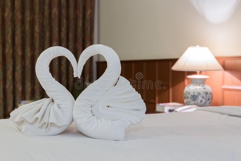 ci?rrese para arriba de dos cisnes agradables de las toallas en cama imágenes de archivo libres de regalías