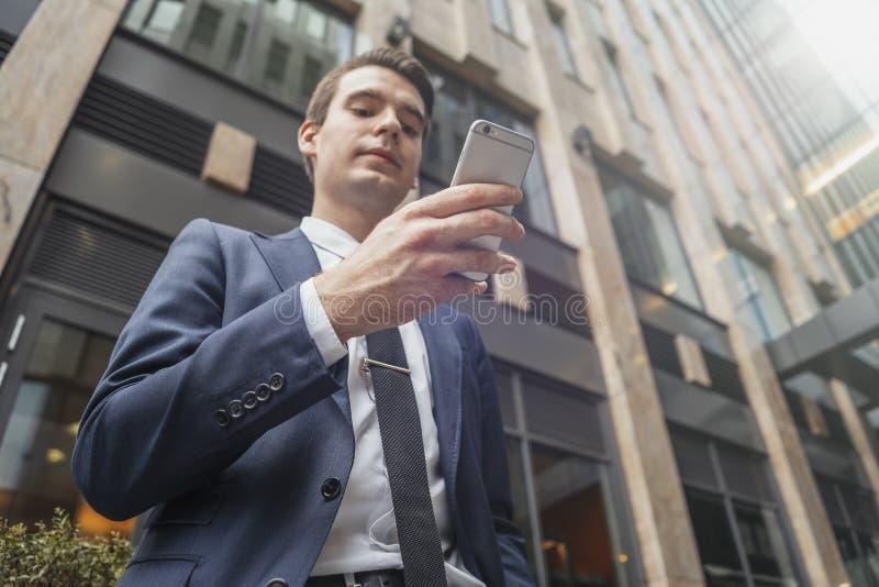 Ci?rrese para arriba de hombre de negocios al lado del rascacielos que mira la pantalla del tel?fono m?vil foto de archivo