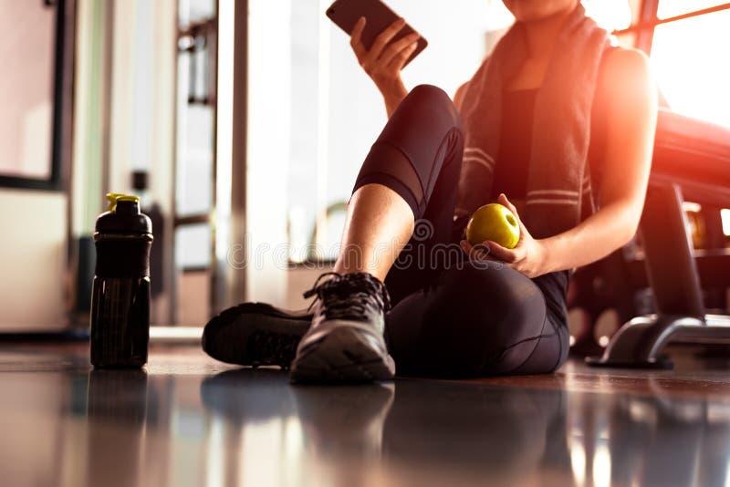 Ci?rrese para arriba de la mujer que usa el tel?fono elegante y sosteniendo la manzana mientras que entrenamiento en gimnasio de  fotos de archivo