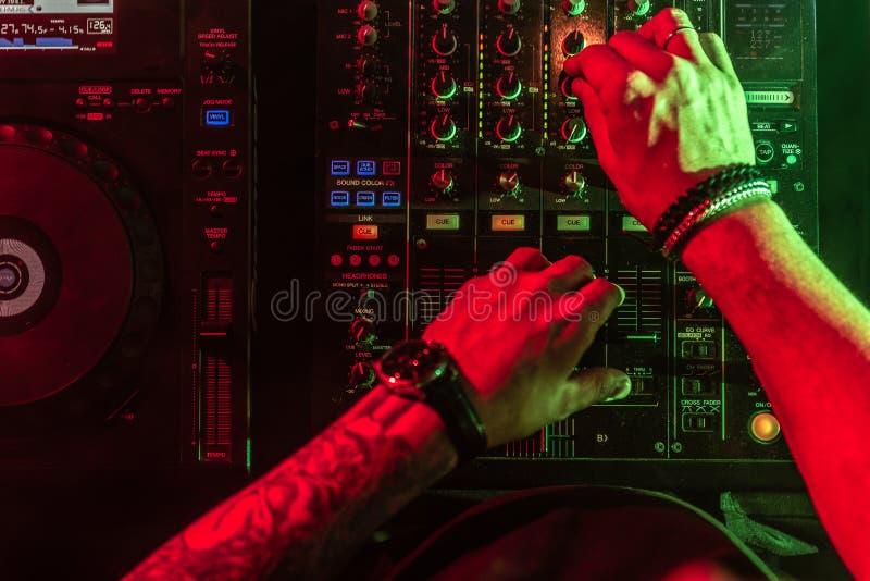Ci?rrese para arriba de las manos de DJ que controlan la tabla de la m?sica en un club nocturno fotografía de archivo