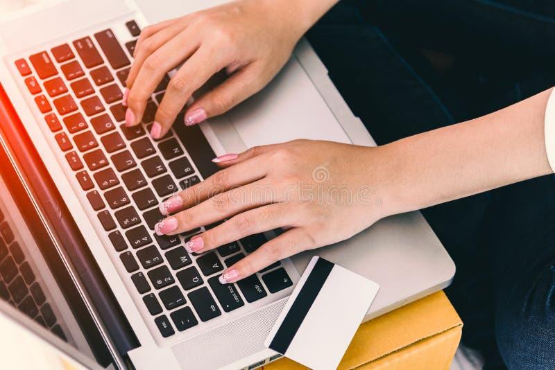 Ci?rrese para arriba de las manos de la mujer usando el ordenador port?til con la tarjeta de cr?dito por otra parte Concepto de l foto de archivo