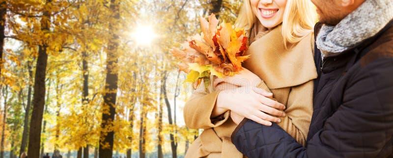 Ci?rrese para arriba de los pares sonrientes que abrazan en parque del oto?o imágenes de archivo libres de regalías