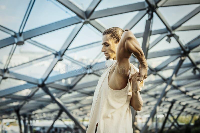 Ci?rrese para arriba de yoga practicante del hombre atl?tico en parque moderno debajo de la b?veda de cristal fotos de archivo libres de regalías