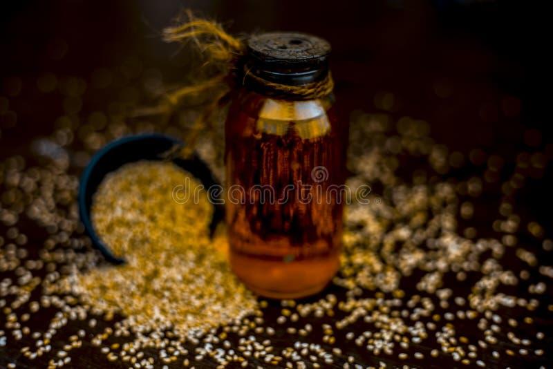 Ci?rrese para arriba del aceite esencial de las semillas de s?samo o hasta o tal con las semillas de s?samo crudas en un cuenco c imagen de archivo libre de regalías