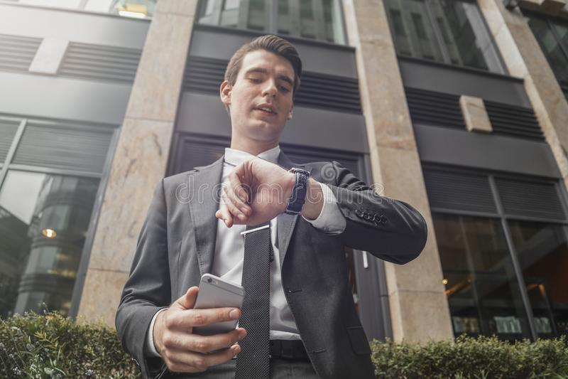 Ci?rrese para arriba del hombre de negocios que sostiene el tel?fono m?vil disponible y que mira los relojes fotos de archivo