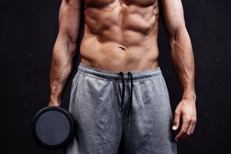 Ci?rrese para arriba del individuo muscular del culturista que hace ejercicios con los pesos sobre fondo negro imagenes de archivo