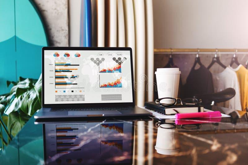 Ci?rrese para arriba del ordenador port?til con los gr?ficos, las cartas, el horario en la pantalla, el cuaderno y la taza de caf fotos de archivo libres de regalías