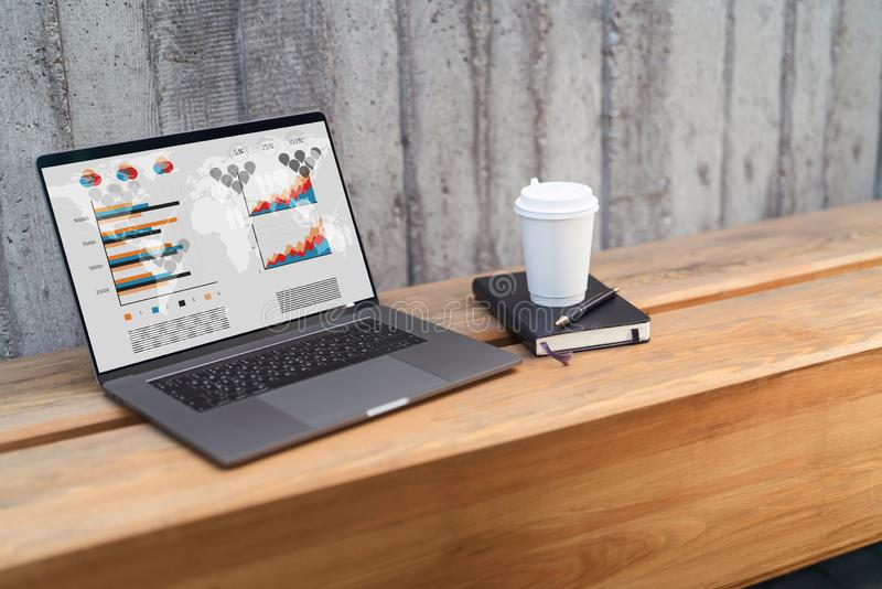 Ci?rrese para arriba del ordenador port?til con los gr?ficos, las cartas, los horario en la pantalla y la taza de caf? en el banc foto de archivo