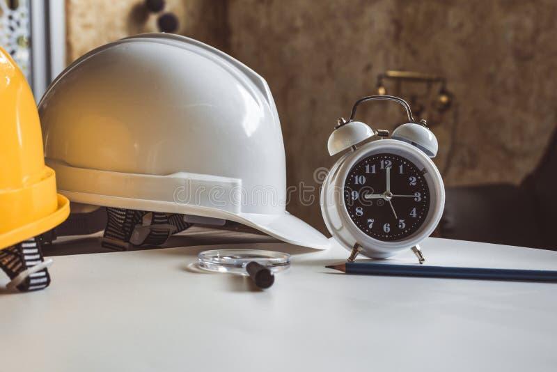 Ci?rrese para arriba del reloj y de dirigir el casco de seguridad en la tabla del modelo Arquitectura y concepto del equipo de la fotografía de archivo