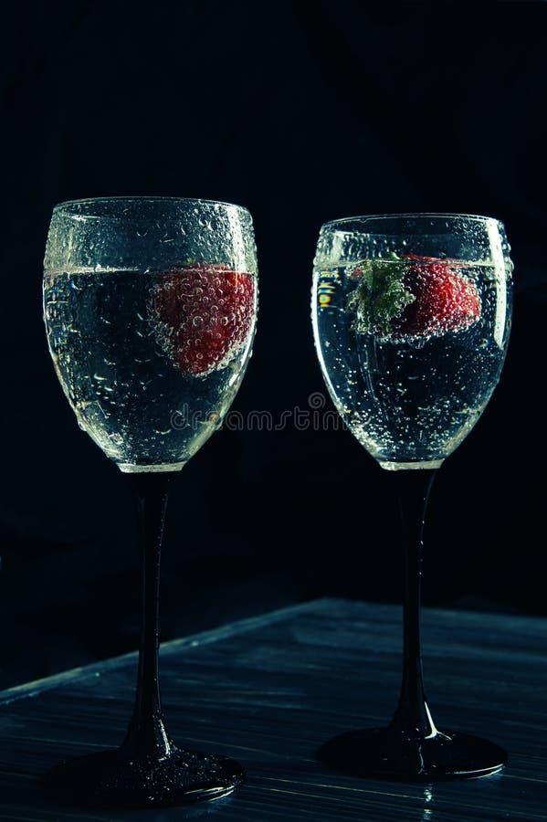 Ci?rrese para arriba, macro Copas de vino llenadas de la bebida chispeante Las fresas flotan en el líquido que chisporrotea Aisla foto de archivo libre de regalías