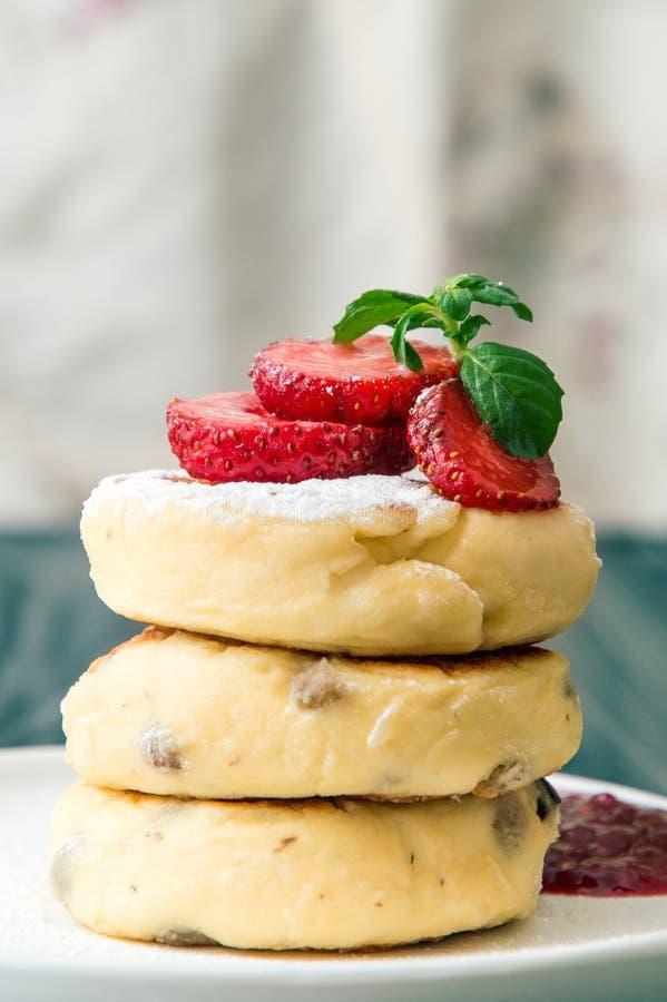 Ci?rrese para arriba, macro Tortas recién hechas del queso con las pasas, vertidas con crema y adornadas con las fresas Copie el  imagen de archivo libre de regalías