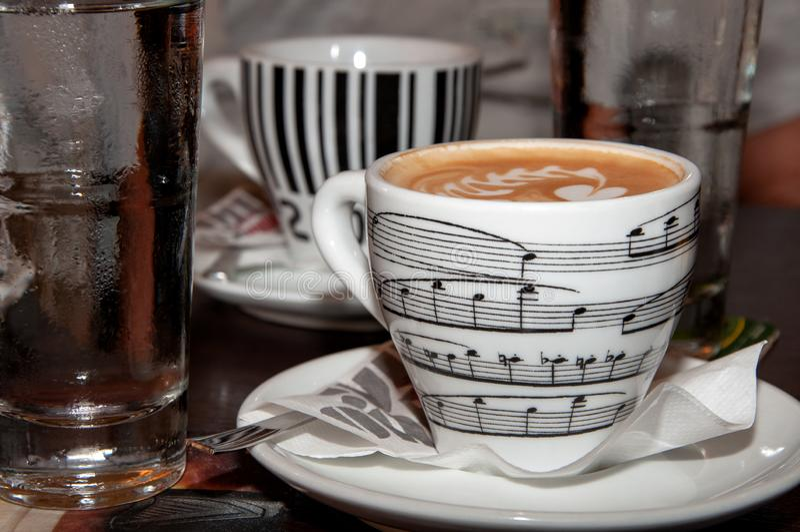 Ci sono due tazze di caffè bianche e un bicchiere d'acqua sulla tavola nel caffè le tazze stampa un frammento di musica e del cod fotografia stock