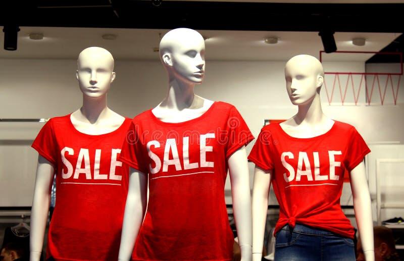 Ci sono tre manichini nel negozio in una maglietta rossa con la vendita di parole fotografie stock