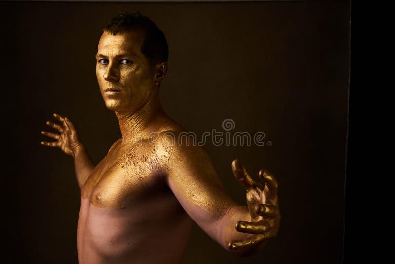 Ciało sztuki farba z złotem na twarzy mężczyzna nad ciemnym tłem zdjęcia stock