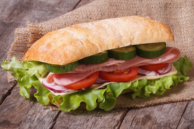 Ciabatta三明治用火腿和菜在一张老木桌上 免版税图库摄影