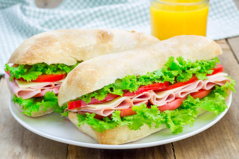 Ciabatta面包三明治用火腿和乳酪在白色板材 图库摄影