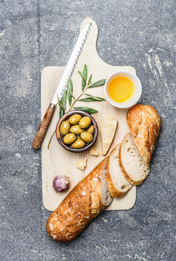 Ciabatta bread cut in slices with olives, oil, garlic and cheese on rustic gutting board , top view royalty free stock photo