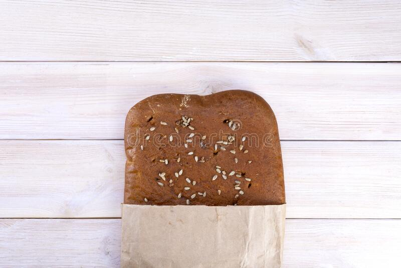 Ciabatta bread with seeds in a paper bag on a light rustic background stock photos