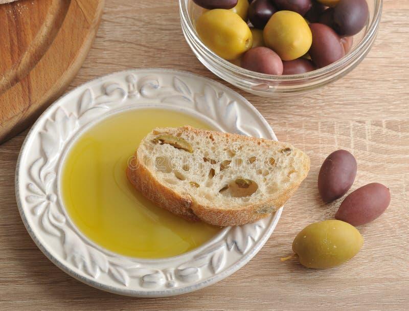 Ciabatta cortado del pan en tablero redondo, aceitunas y ol virginal adicional fotografía de archivo