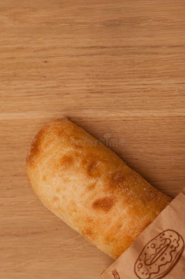 Ciabatta in einer Papiertüte auf einem Holztisch lizenzfreies stockbild