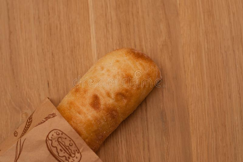 Ciabatta in einer Papiertüte auf einem Holztisch, Draufsicht stockfotografie