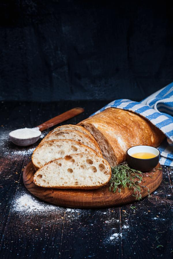 Sliced homemade italian ciabatta bread with olive oil on dark background. Ciabatta, herbs, olive oil, flour. Close up view, copy s stock photo