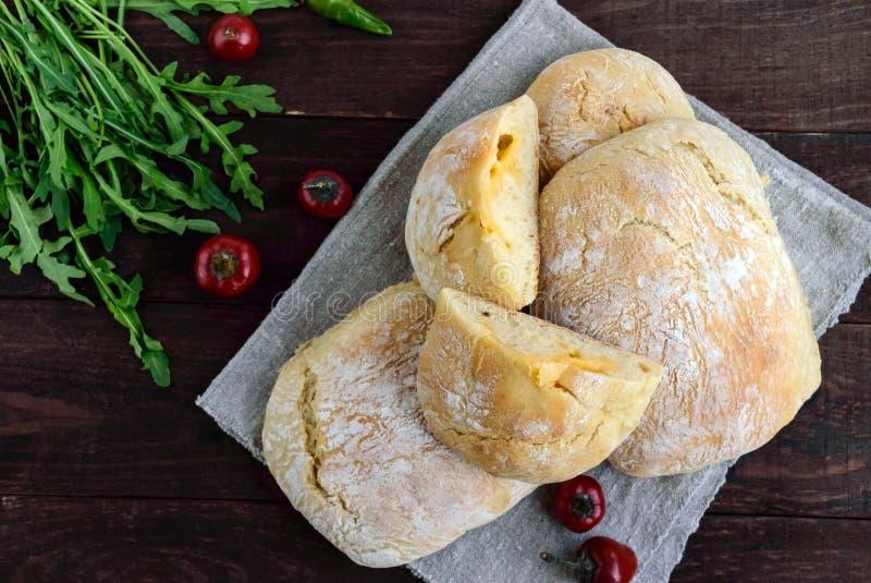 Ciabatta mit dem Käseanfüllen - frisch gebackenes italienisches Weißbrot auf einem dunklen hölzernen Hintergrund stockfoto