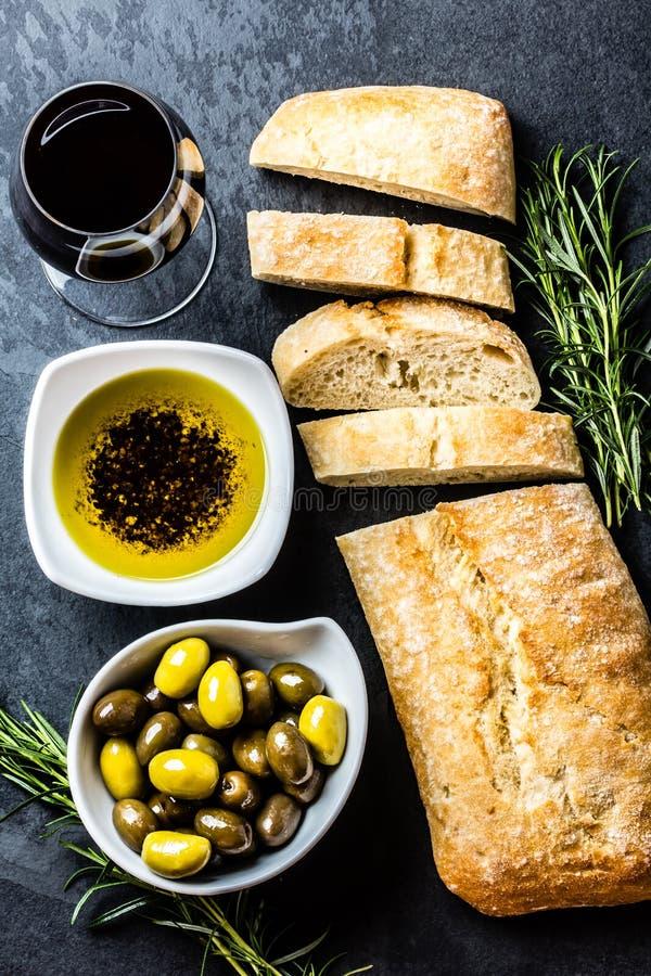 Ciabatta, peperolie, olijven, arugula, rozemarijn, leiachtergrond stock foto's