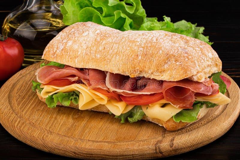 Ciabatta sandwich with lettuce , prosciutto and  cheese on wooden board. Ciabatta sandwich with lettuce , prosciutto and cheese on wooden board stock images