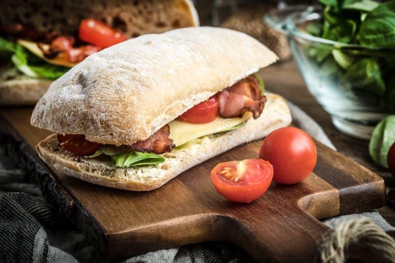 Ciabatta-Sandwich mit Arugulasalat, Speck und gelbem Käse lizenzfreie stockfotografie