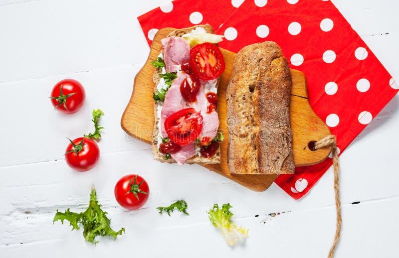 Ciabattasandwich met prosciutto, kersentomaten en salade op witte houten achtergrond stock foto