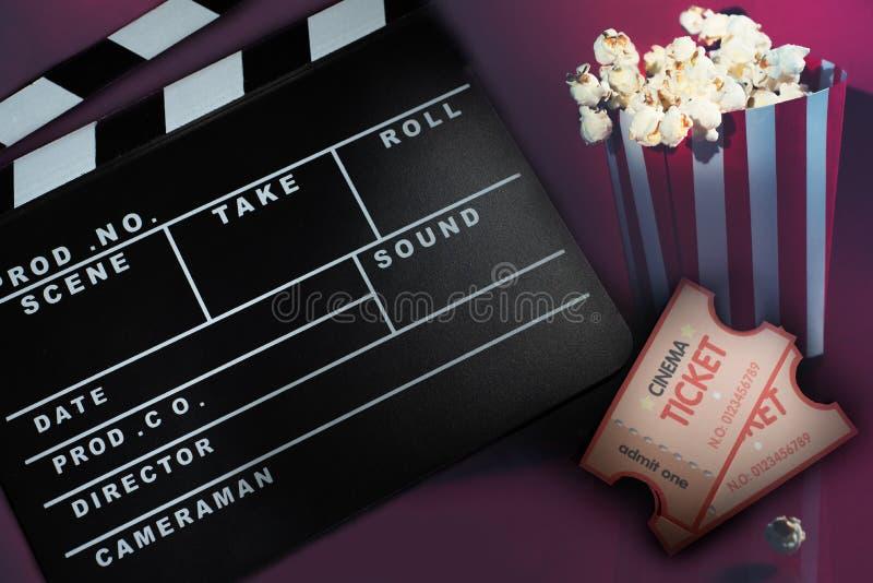 Ciack和戏院的玉米花在红色背景 免版税库存图片