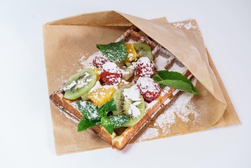 Cialda belga con frutta e zucchero in polvere su un fondo bianco fotografie stock libere da diritti