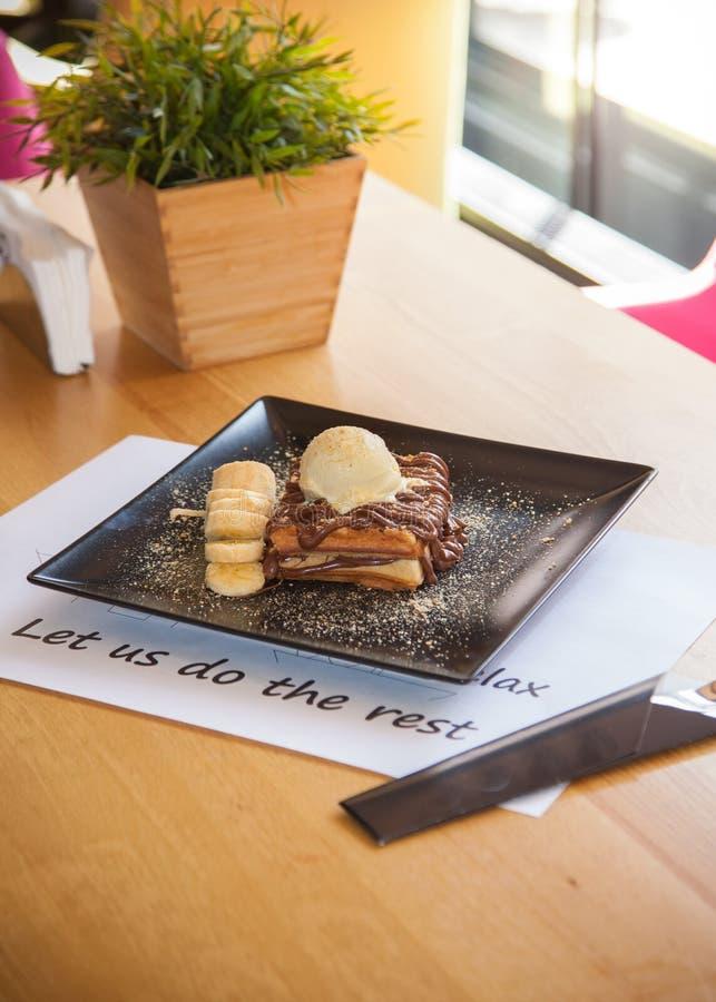 Cialda del cioccolato completata con la decorazione del gelato e della banana sopra fotografia stock libera da diritti