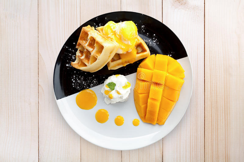 Cialda di vista superiore con il gelato ed il mango sulla tavola di legno fotografie stock