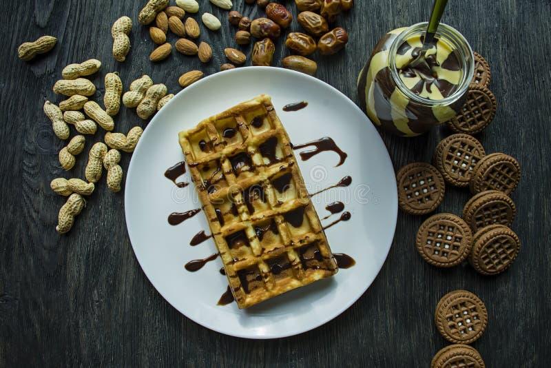 Cialde belghe tradizionali coperte in cioccolato su un fondo di legno scuro Prima colazione saporita Decorato con i dadi di rasch immagini stock libere da diritti