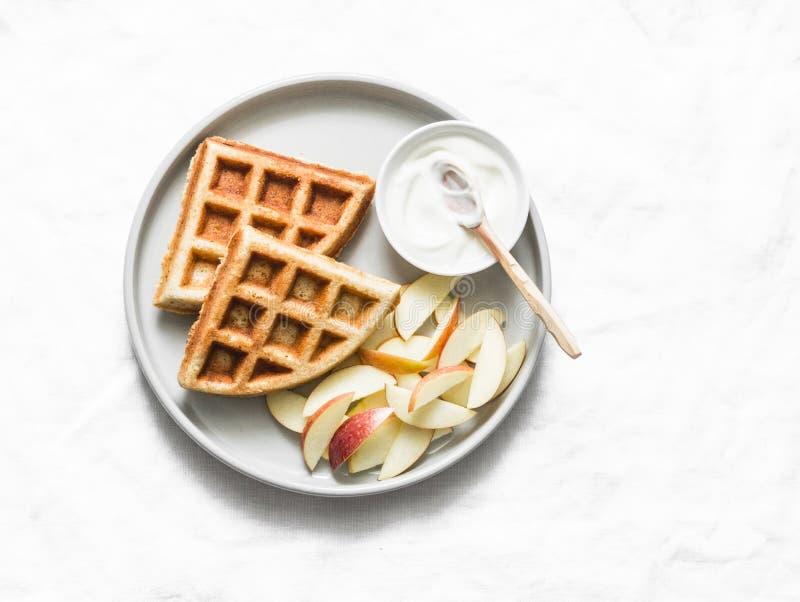 Cialde della farina d'avena della banana con la mela ed il yogurt su un fondo leggero, vista superiore Prima colazione deliziosa, immagini stock libere da diritti