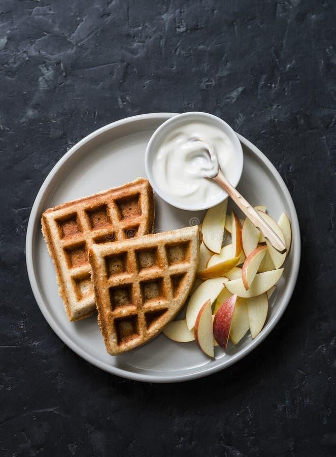 Cialde della farina d'avena della banana con la mela ed il yogurt su un fondo scuro, vista superiore Prima colazione deliziosa, d immagini stock libere da diritti