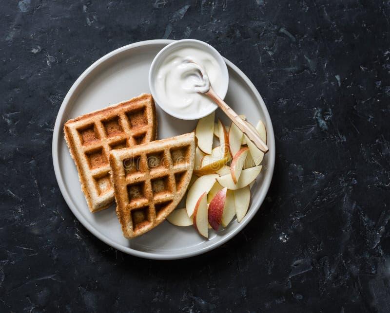 Cialde della farina d'avena della banana con la mela ed il yogurt su un fondo scuro, vista superiore Prima colazione deliziosa, d fotografia stock libera da diritti