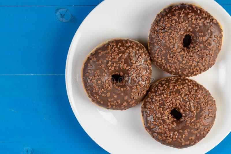Ciambella con cioccolato che completa crema sui precedenti blu fotografia stock libera da diritti