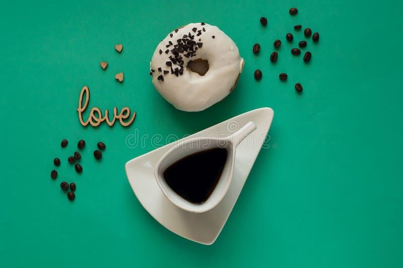 Ciambella con glassa bianca e la bella tazza bianca con caffè sul fondo con i chicchi di caffè, concetto della prima colazione va fotografia stock
