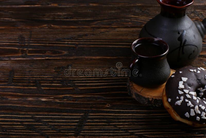 Ciambella con glassa e cioccolato in polvere nero e una tazza autentica di forte caffè Una latta dei chicchi di caffè e dei grani fotografia stock
