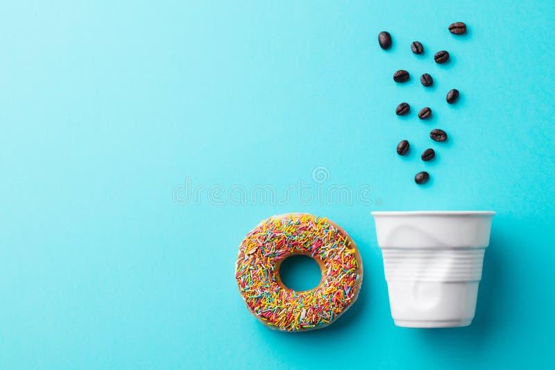 Ciambella con il fagiolo bianco dei chicchi di caffè e della tazza su fondo blu Copi lo spazio fotografia stock libera da diritti