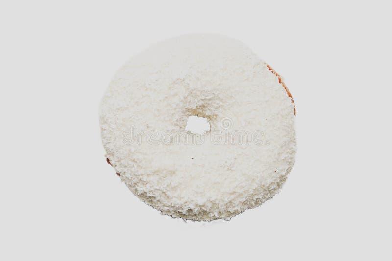 Ciambella con la guarnizione della noce di cocco sul fondo bianco immagini stock