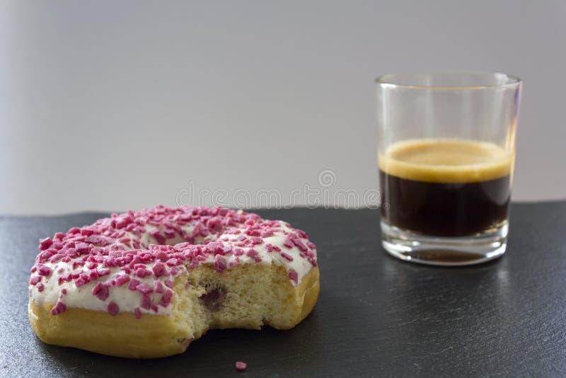 Ciambella della fragola con la sig.na del morso e una tazza del caffè del caffè espresso fotografia stock
