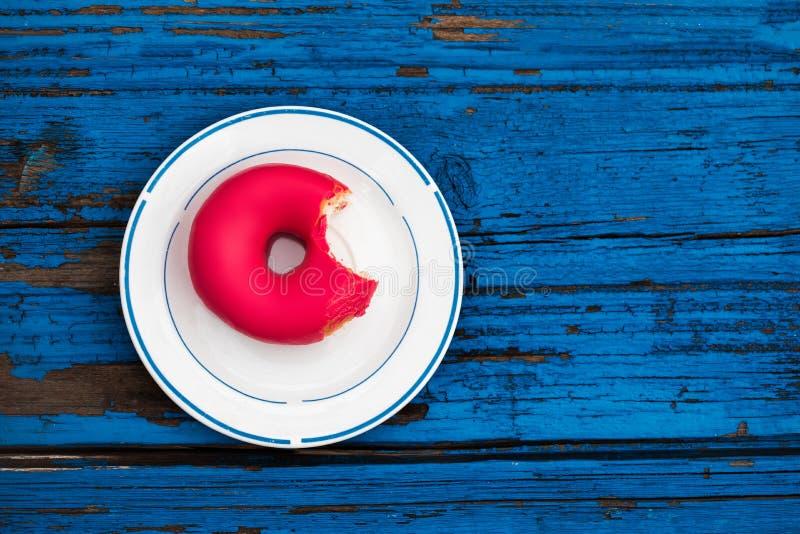 Ciambella di Bited su un piatto su fondo di legno blu variopinto Ciambella immagine stock