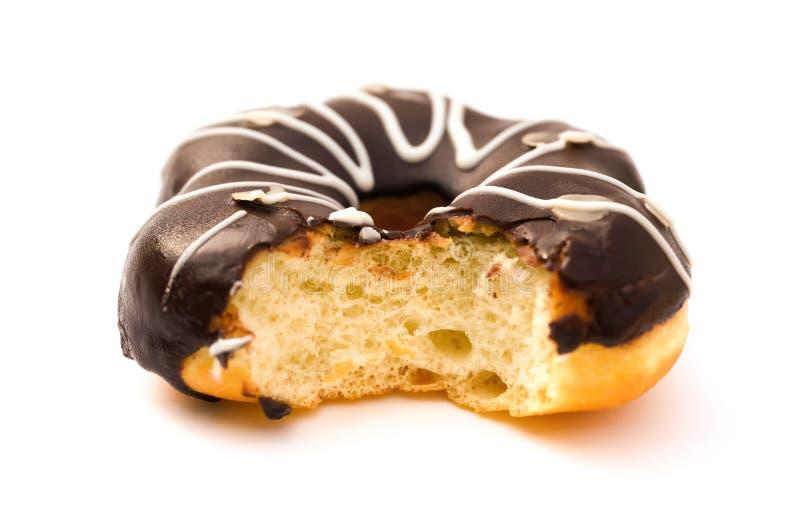 Ciambella di sapore del cioccolato di vista laterale con un morso su bianco fotografia stock libera da diritti