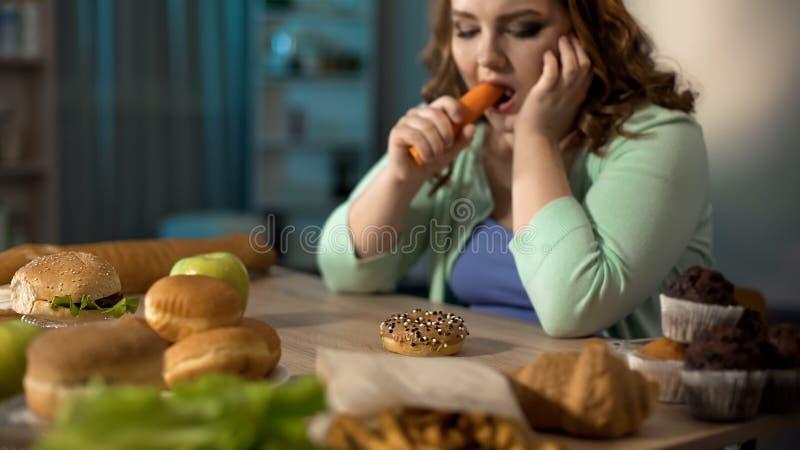 Ciambella femminile obesa depressa della carota di cibo invece ed alimenti a rapida preparazione, stanti a dieta immagine stock