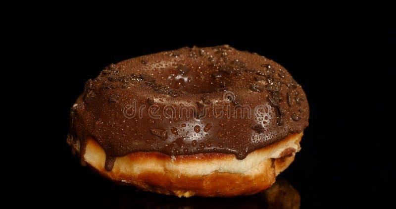 Ciambella lustrata del cioccolato su fondo nero fotografie stock libere da diritti