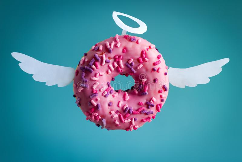 ciambella rosa con le ali di Libro Bianco e nimbus su un fondo blu fotografia stock libera da diritti